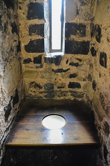 Old stone toilet in the tower of london with wooden floor. medieval latrine in the tower of london.