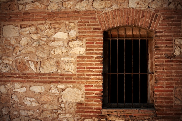 An old stone wall and a window with bars