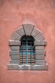 Old stone window in castle. metal bars on window. vertical frame
