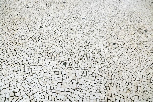 Старая уличная дорога вымощила поверхность дорожки каменной мостовой. брусчатка из гранита