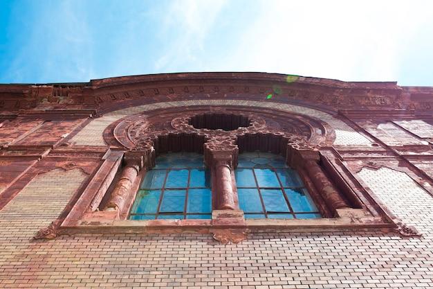 Старое лепное окно на фасаде церкви с солнечными бликами в ужгороде