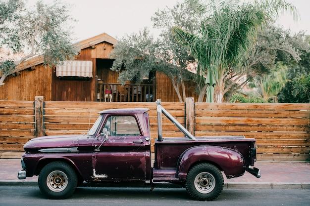 야자수와 집 앞에 서있는 오래 된 스타일의 미국 자동차