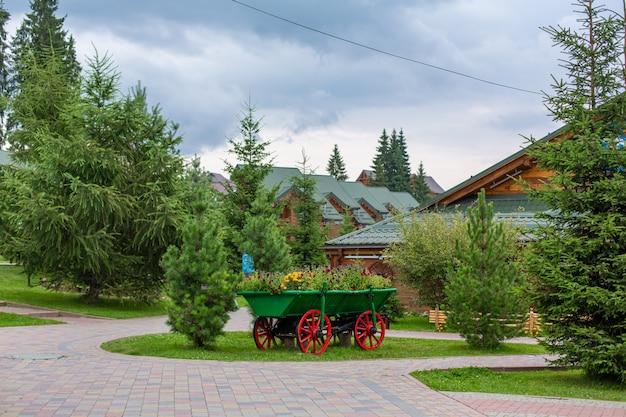 Тележка в старинном стиле с зеленым кустом для украшения двора.
