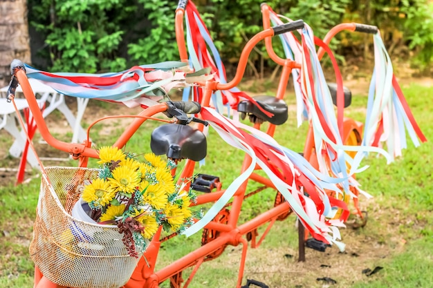 Old style classic bicycle with red and white ribbon on it and flower on the basket