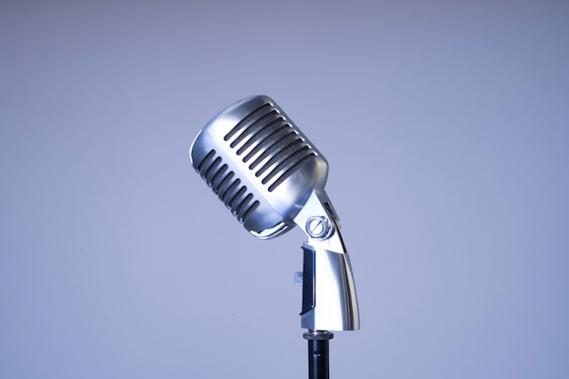 Old style filtered photo of a metallic mic from the side isolated