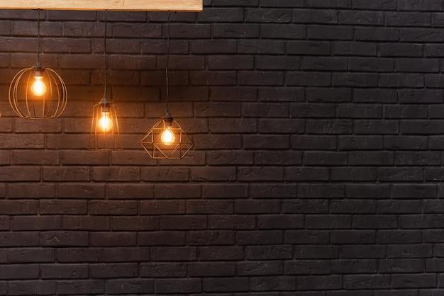 이전 스타일 백열 전구. 어두운 검은 벽돌 벽에 걸려 오렌지 복고풍 램프.
