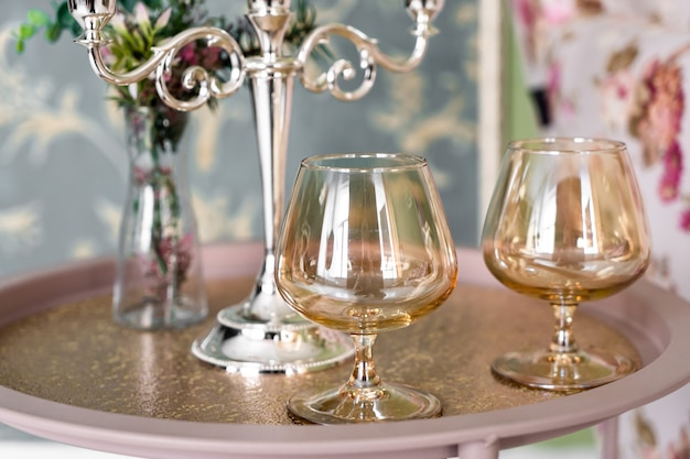 Old style retro candles and wine glass on a tray, vintage home decor on an a table, in light tones