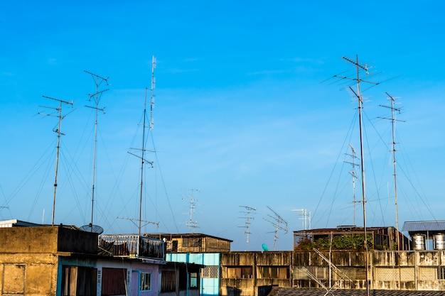 Телевидение в старом стиле (тв) антенна и спутник на крыше с домом или зданием в провинциальном районе в голубом небе с облаками фон в таиланде, панели приемника аналогового телевидения