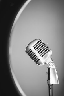 Old style vertical photo of a metallic mic from the side isolated on white background. mcrophone closeup on grey background.