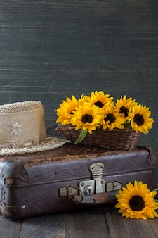 On an old suitcase a bouquet of sunflowers and a straw hat