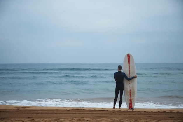 Old surfer with his longboard stays alone on beach in front of ocean and watching waves in ocean before going to surf, wearing full wetsuit in early morning