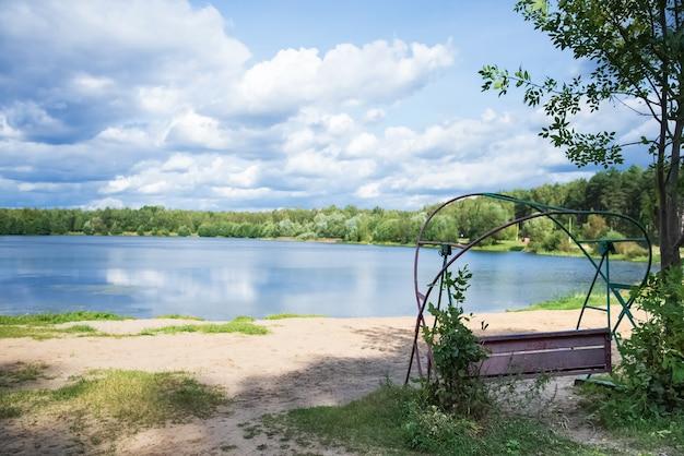 夏の日の風景の砂の湖岸の古いブランコ