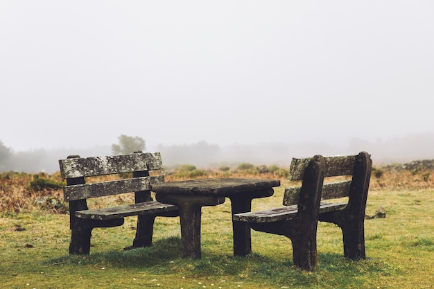 Old table and benches at fanal forest and green hills of madeira island in portugal