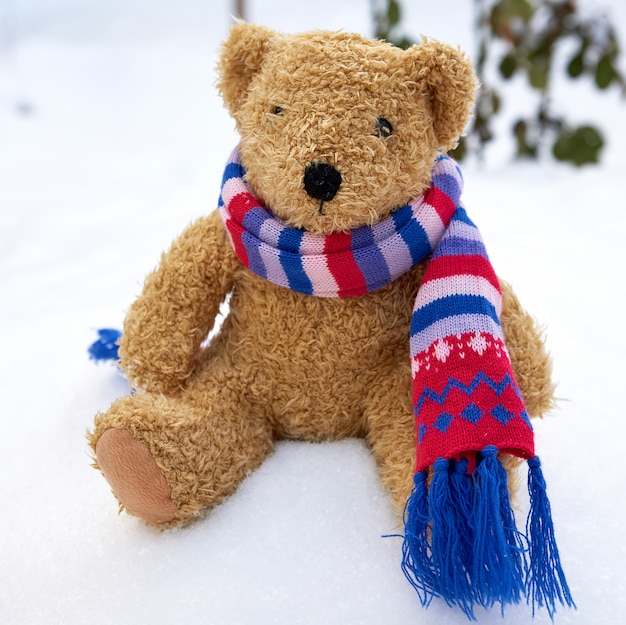 Old teddy bear in a scarf sits on white snow