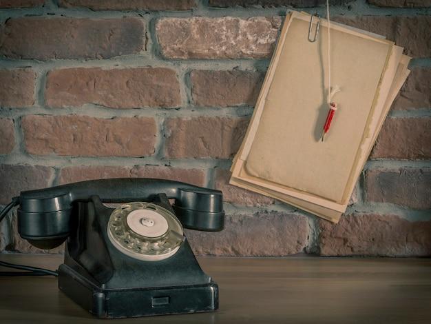 古い電話と鉛筆で紙、レンガの壁の