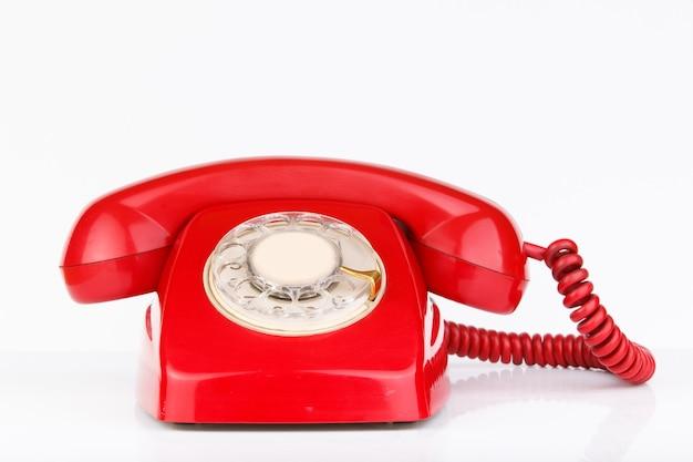붉은 색 흰색 표면에 고립 된 오래 된 전화