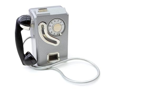 흰색 배경에 고립 된 동전과 함께 사용하기 위해 60 년대에서 설정하는 오래 된 전화. 텍스트를위한 공간. 통신 개념.