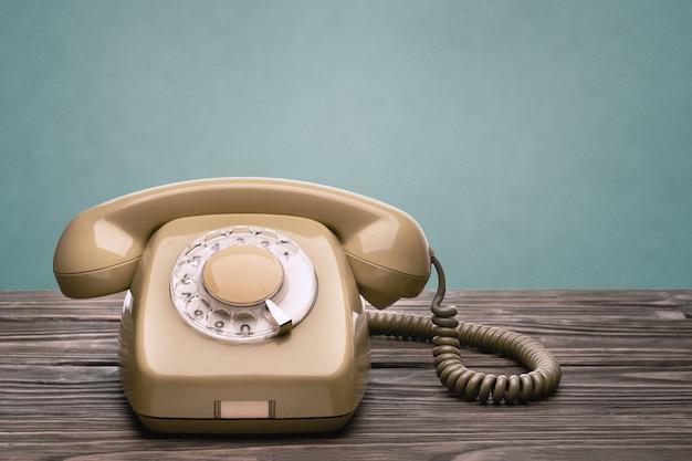 20 세기 70 년대의 오래된 전화기는 파란색 배경에 고립 된 나무 판에 선다.
