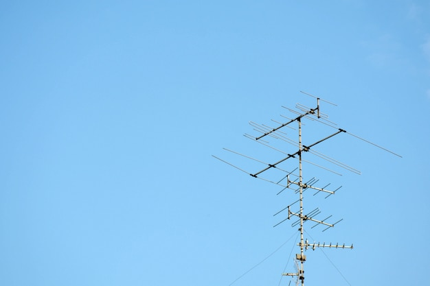 Old televisions antenna on blue sky