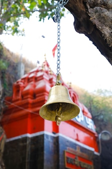 Old temple bell hanging from branch