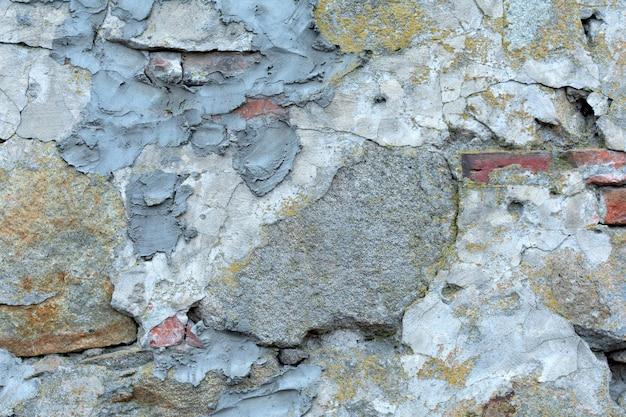 Старая стена текстуры с бетоном, старой штукатуркой, красным кирпичом и зеленым мхом. грандж текстуры для украшения