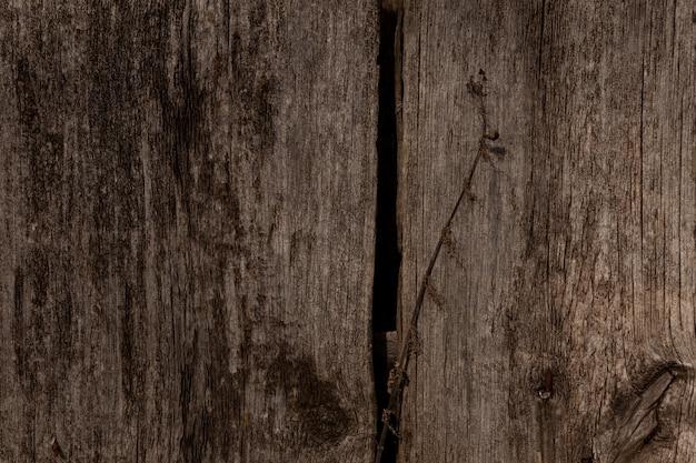 ひび、結び目、さびた釘のある古い質感のダークウッドの表面。柵の断片またはカラマツの板の自然な背景。