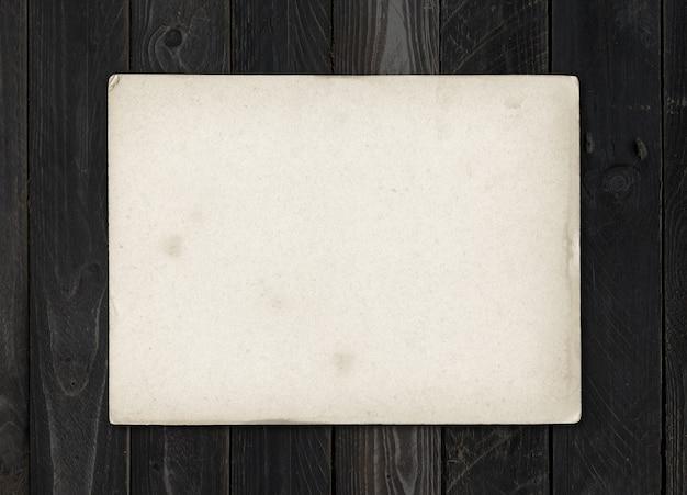 Старый текстурированный лист бумаги на черном деревянном столе.