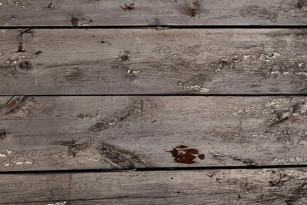 ひび、結び目、さびた釘、剥がれたペンキのある古い織り目加工の木材表面。カラマツの板の自然な背景。