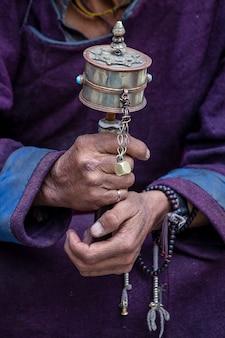 인도 라다크 헤미스 수도원에서 불교 기도 바퀴를 들고 있는 늙은 티베트 여성. 손과 기도 바퀴, 클로즈업
