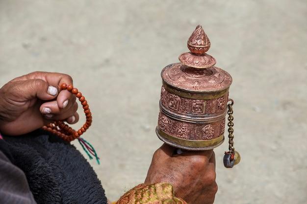 인도 라다크 수도원에서 불교 기도 바퀴를 들고 있는 늙은 티베트 여성이 가까이 있습니다.