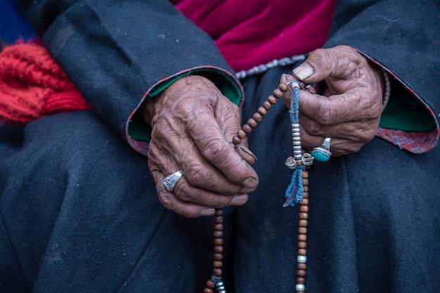 인도 라다크 헤미스 수도원에서 불교 묵주를 들고 있는 늙은 티베트 여성. 손과 묵주