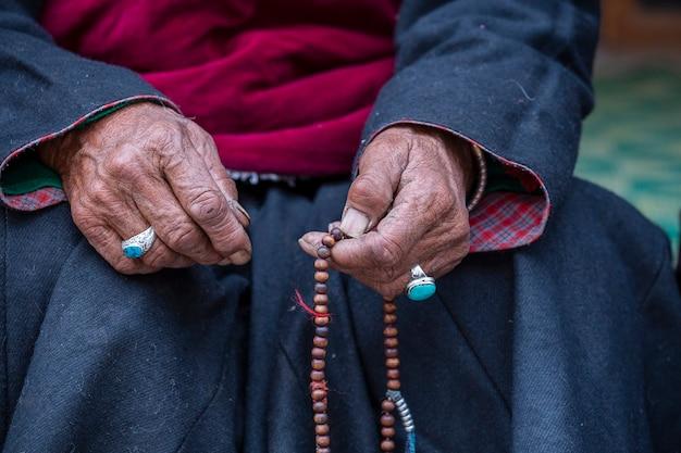 인도 북부의 헤미스 수도원, 라다크, 잠무, 카슈미르 주에서 불교 묵주를 들고 있는 늙은 티베트 여성. 손과 묵주, 클로즈업