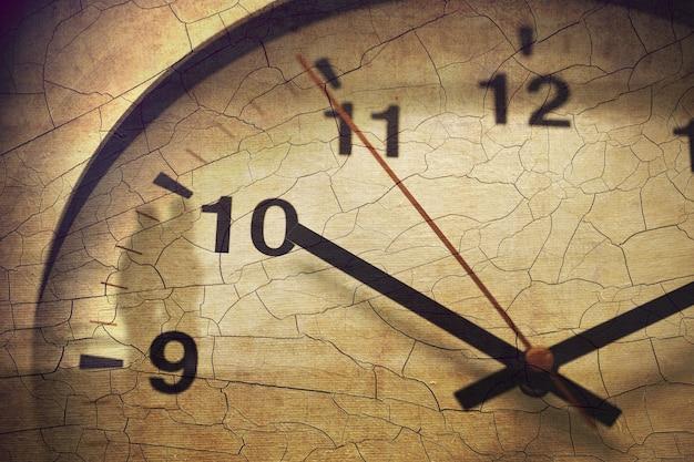 昔の死や永遠の時間、歴史の時代のアンティークレトロなコンセプト、ひびの入ったグランジテクスチャオーバーレイ壁時計のクローズアップを亡くします。