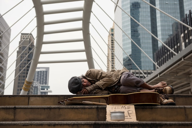 Old tired beggar or homeless man sleep on stair of modern city with guitar, donate bowl, paper cardboard with help text in winter. social issue for retired elderly but have no money.