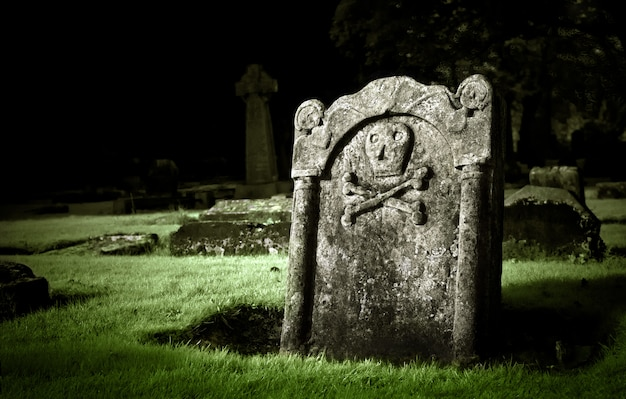 Old tombstone with skull and bones in a graveyard