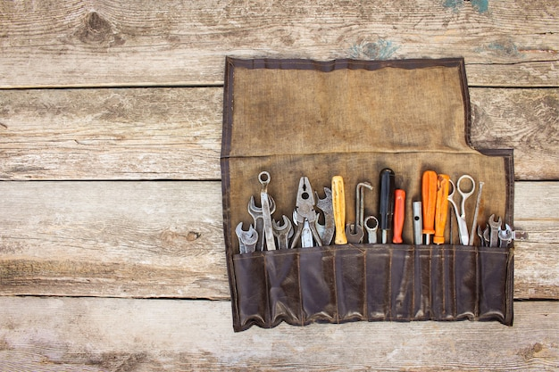 Old tools in bag on wooden background. top view