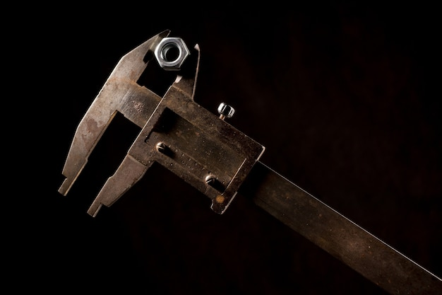Old tools caliper with screw-nut in front of a black