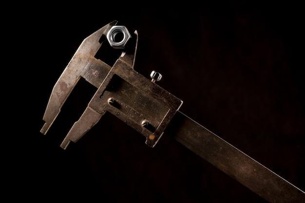 블랙 앞의 나사 너트가있는 오래된 도구 캘리퍼스
