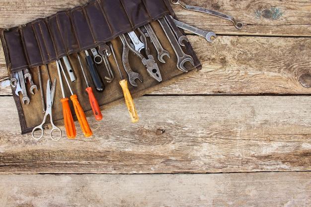 Старые инструменты в сумке на деревянных фоне. вид сверху Premium Фотографии