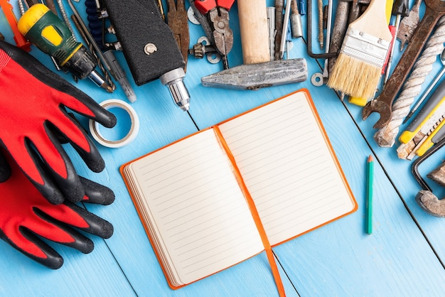 Старые инструменты на рабочем столе с блокнотом для рисования