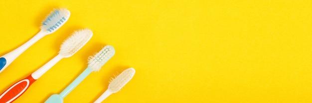 黄色の背景に古い歯ブラシ
