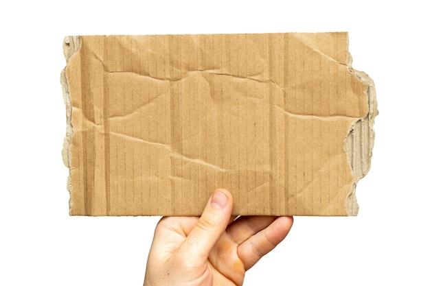 旧的撕裂硬纸板片在纸上的手与复制空间
