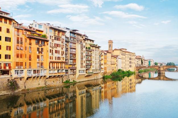 Старые городские дома, отражающиеся в водах реки арно в летний день, флоренция, италия