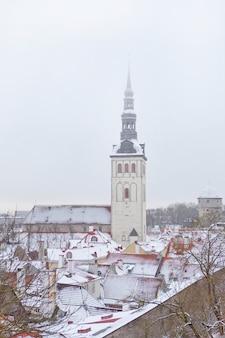 에스토니아 탈린의 구시가지. 성 니콜라스 교회, niguliste 외관의 세로 사진. 겨울 시간에 구시 가지의 눈과 지붕