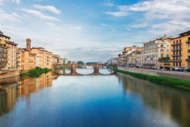 Старый город с мостом санта-тринита, отражающимся в воде реки арно, флоренция, италия