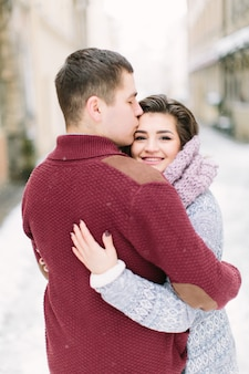 In old town. young cheerful caucasian couple in warm cozy clothes walking in city centre.