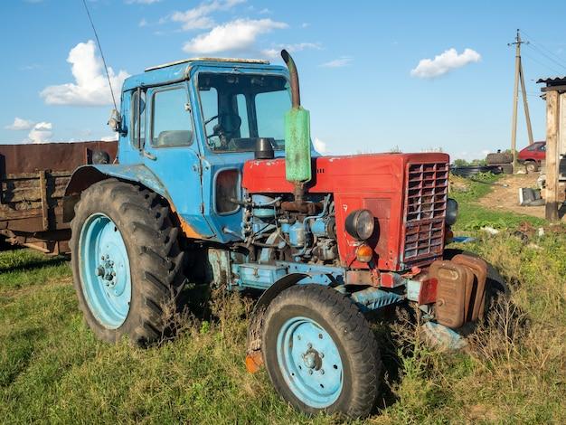 夏の晴れた日にiackyardにある古いトラクターの青い駐車場