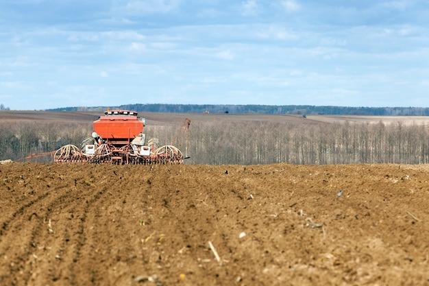 春の季節に小麦を収穫する古いトラクター。