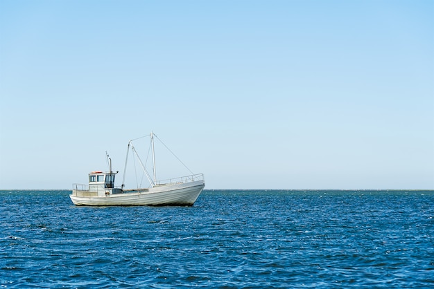 Old traditional for baltic sea or scandinavian countries vintage fishing boat in sea. minimalist shot.