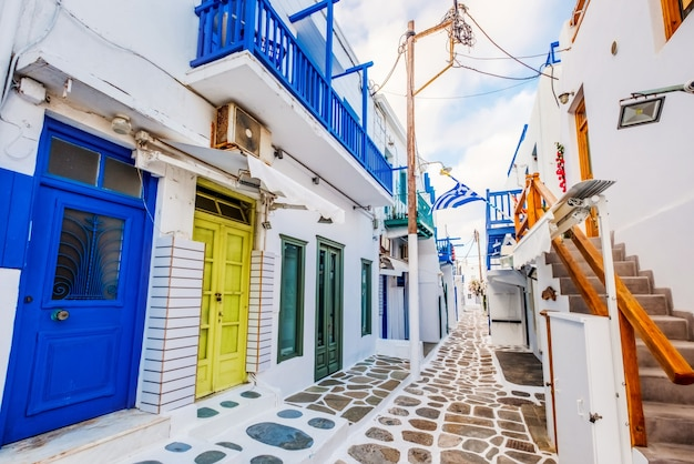 Old traditional greek street of mykonos with white houses colourful doors